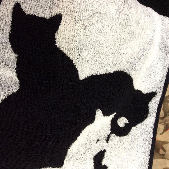 大西賢の今治フェイスタオル黒猫白猫シルエットの白地の猫が手をなめている柄部分のクローズアップ画像