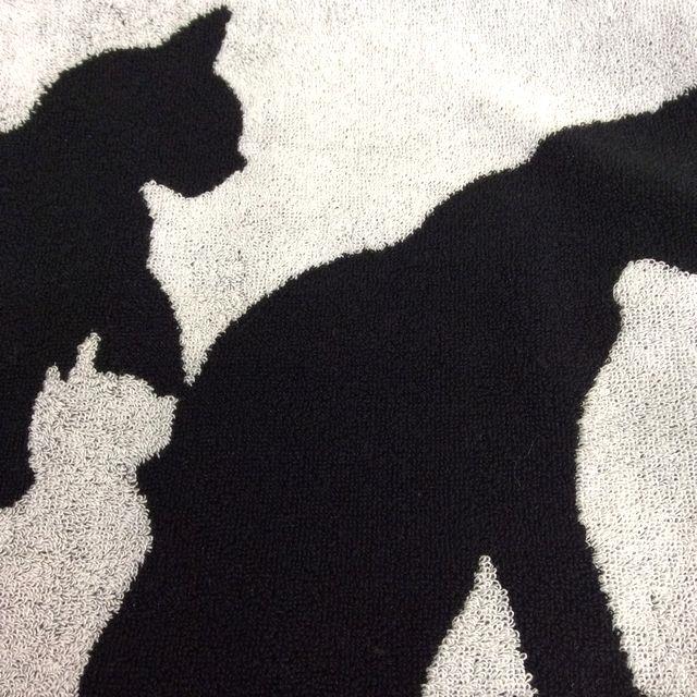 大西賢の今治フェイスタオル黒猫白猫シルエットの上白地の猫柄のクローズアップ画像