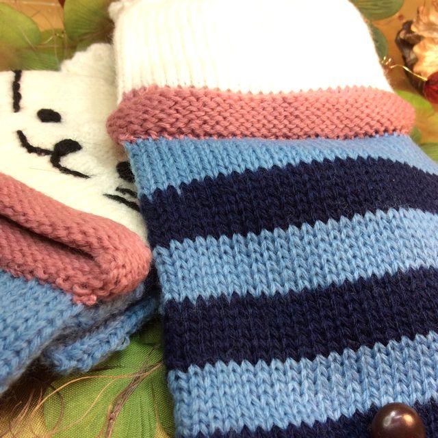 カオニャン手袋の、片方は猫の顔を刺繍してある部分が見える様に置いて、もう片方は指に蓋の部分を被せて、置いた画像
