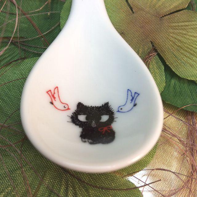 カトウシンジ黒猫ティースプーンの青い鳥と赤い鳥の真ん中に座る黒猫スプーンのクローズアップ画像