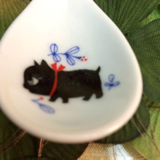 カトウシンジ黒猫ティースプーンの黒猫が横向いていて、赤い花があるティースプーンのクローズアップ画像