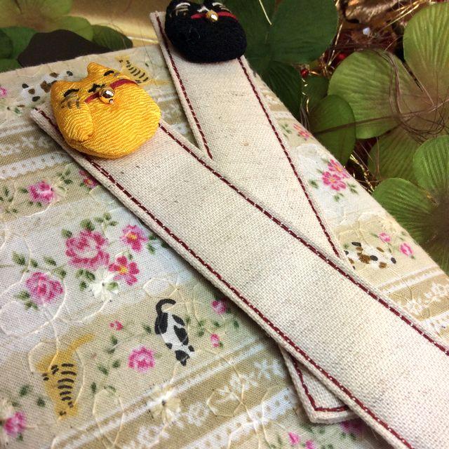 ドン・ヒラノさんのおしゃれな布しおり招き猫の黒色と黄色を文庫本の上に置いた画像