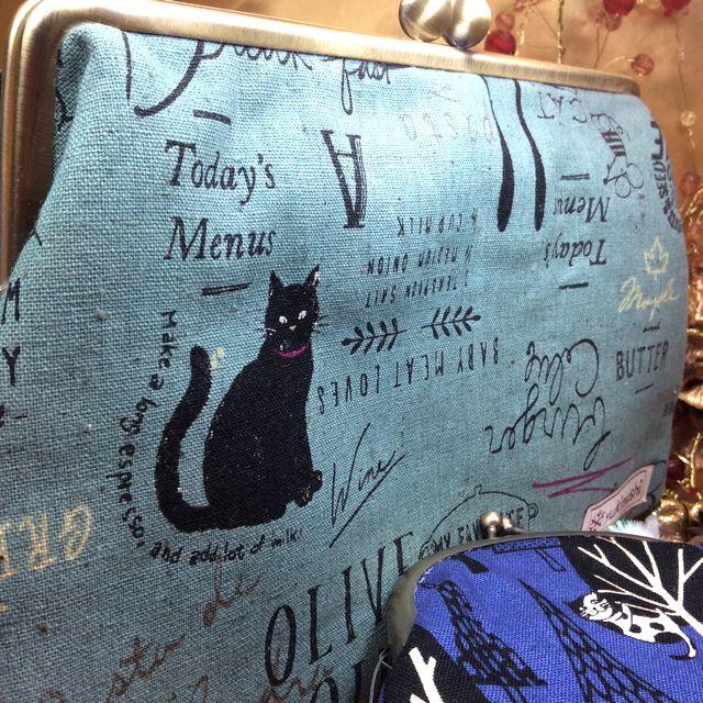 ハンドメイドアーチスト「ゆきむし」さんの猫柄親子がま口クラッチバッグのモスグリーン色の大きさを比較するために、手前に小銭入れがま口を置いた全体の画像