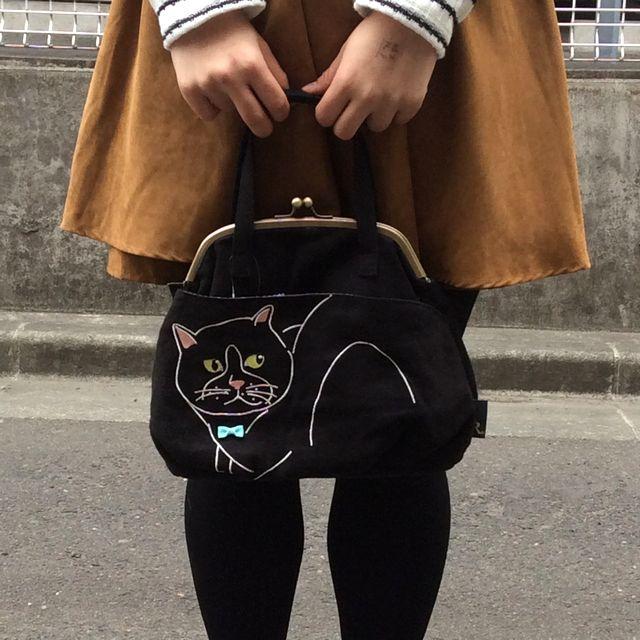 ルートート黒猫がま口バッグの前側を表側にして人物との大きさの比較のために手で持っている状態の画像