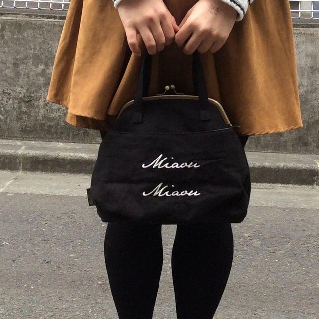 ルートート黒猫がま口セカンドバッグの後ろ側を表にして手で持った状態の画像