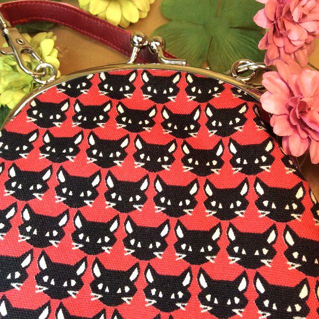 ゆきむしさん作ハンドメイドがま口ポーチ地色朱色で黒猫が整列している商品のアップ写真