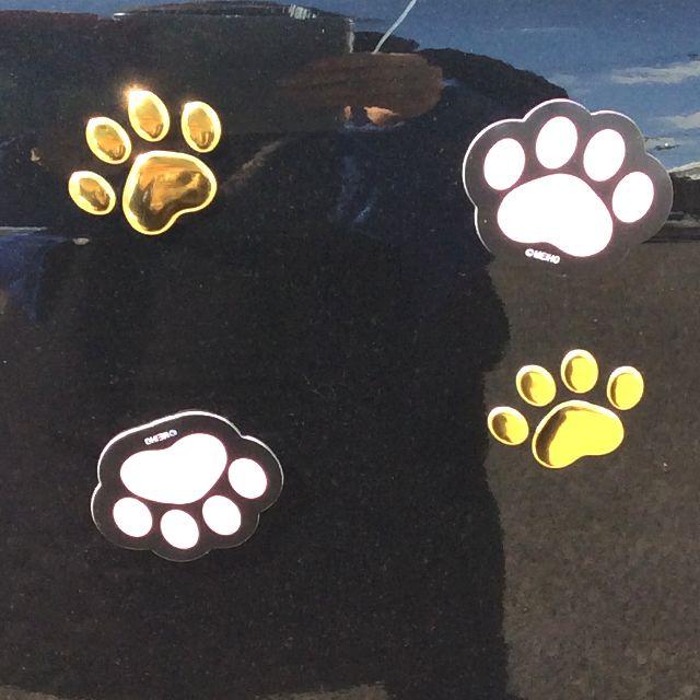 猫の肉球マグネットのピンク色と猫の肉球ステッカーのゴールド色のSサイズを大きな青い馬の車に張ったところのアップ写真