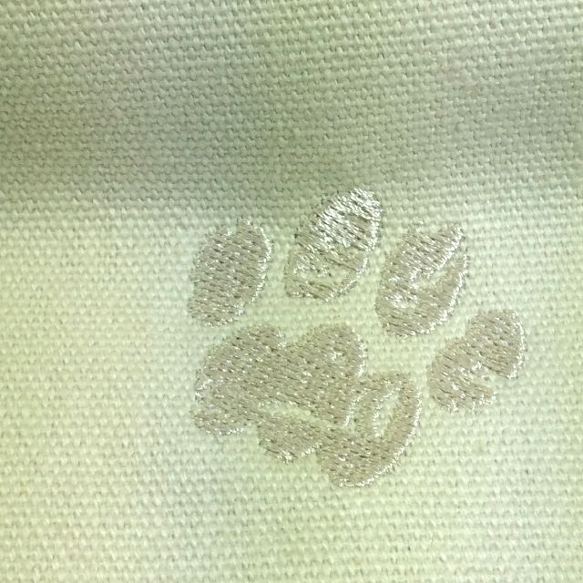 ルートートのがま口型ハンドバッグ背面で右下隅に刺繍された肉球マークをクローズアップした画像。