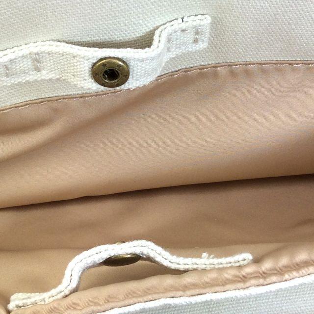 ルートートのがま口型ハンドバッグ背面にあるポケットを開いた画像。ポケットにはスナップボタンが付いている。