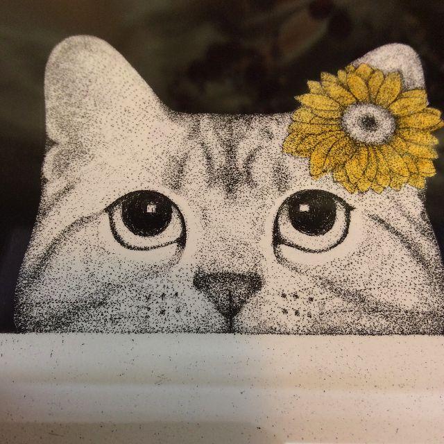 東マユミ銅版画「なにみてるの」の黄色い花を頭に付けた猫のクローズアップ画像