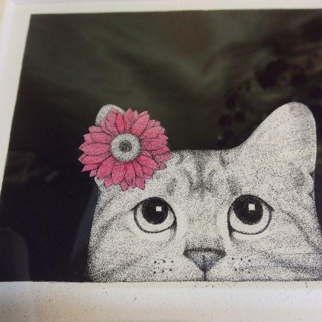 東マユミさんの銅版画「なにみてるの」のピンクの花を頭に付けた猫の画像