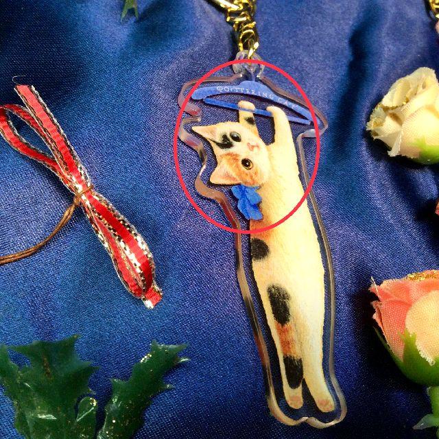 ポタリングキャットアクリルキーホルダー三毛猫の青いハンガーとリボン部分のクローズアップ画像