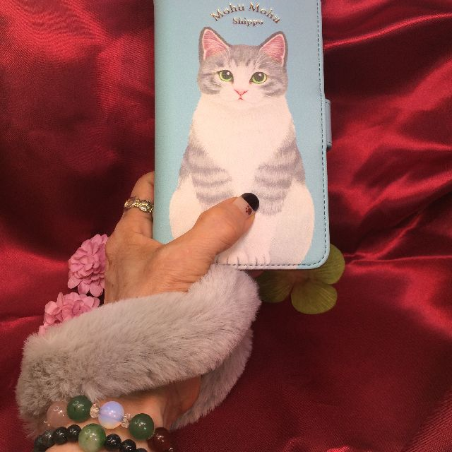 フェリシモ猫部のブック型スマホケース尻尾付きのストラップシッポを、手に巻き付けた画像