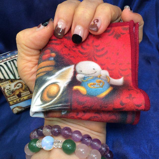 猫のダヤンのメガネ拭き「赤い部屋のマカロン」を畳んで手の平に載せた画像