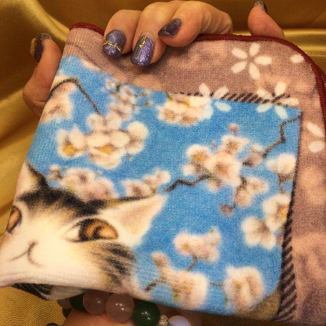 猫のダヤンのタオルハンカチ「桜色の風」を掌に載せた画像