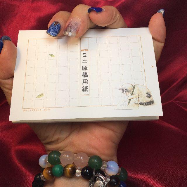 ポタリングキャットのメモ帳「ミニ原稿用紙」を掌に載せた画像