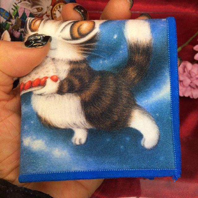ダヤンのメガネ拭き「青い星のケーキ」を手の平に載せた画像